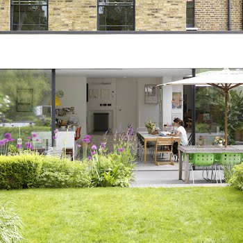 The kitchen, dining and living area spills out into the garden, with the granite patio mimicking the poured concrete floor inside. A Habitat table and Robin Day chairs provide dining space in summer.